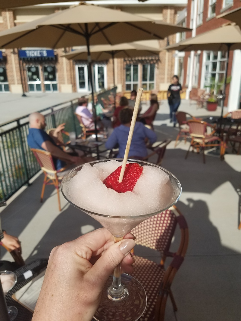 Frosé in martini glass in foreground and patio in background with guests blurred in distance