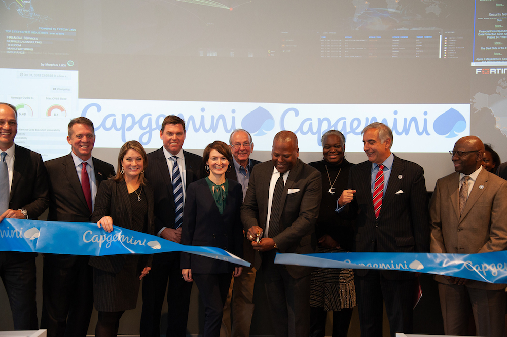 Leaders line up behind a wide blue ribbon with the Capgemini logo on it, with global Security Operations Center screen behind them, as Mayor Steve Benajmin cuts ribbon